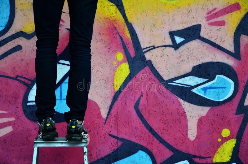 Młody graffiti artysta maluje nowego graffiti na ścianie Fotografia proces rysować graffiti na ściennym zakończeniu obraz stock