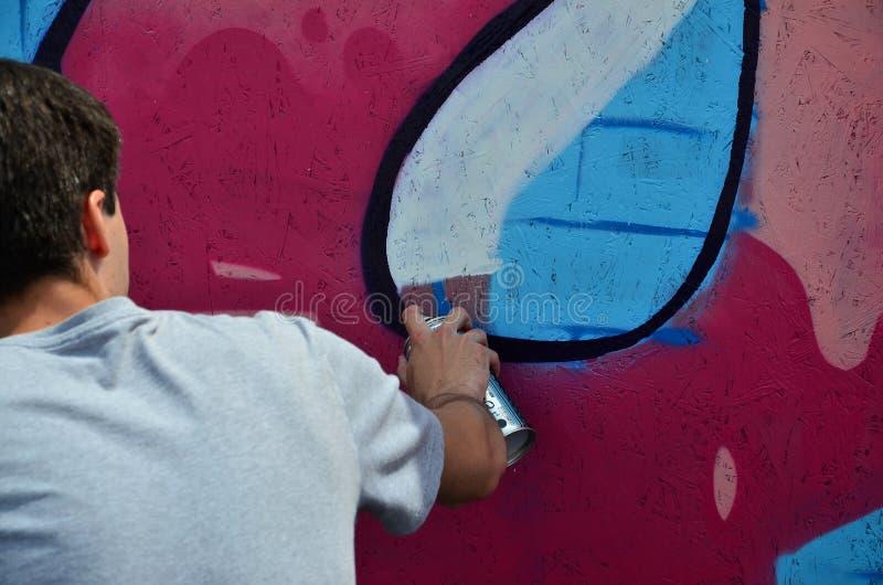 Młody graffiti artysta maluje nowego graffiti na ścianie Fotografia proces rysować graffiti na ściennym zakończeniu obrazy stock
