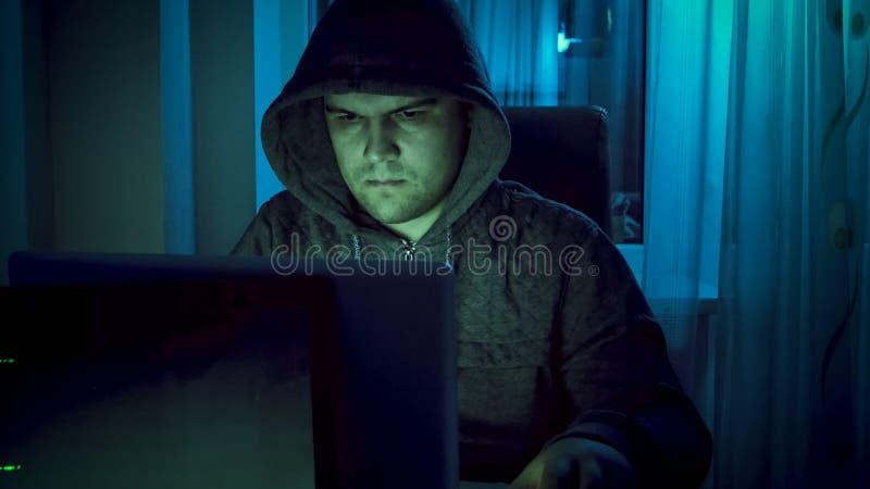 Młody hacker w hoodie pracuje na komputerze przy nocą obraz stock