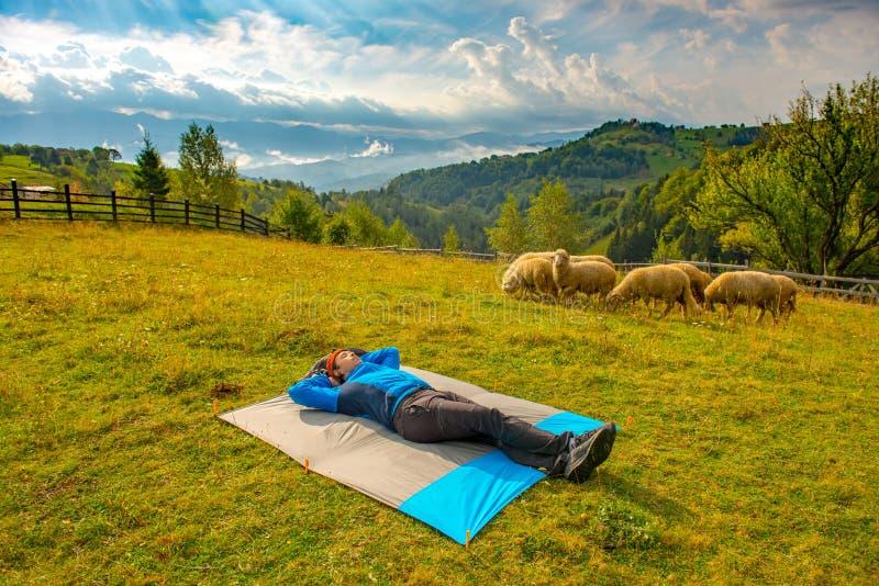 Młody halny wycieczkowicz odpoczywa na wodoodpornej nylonowej koc w pięknym góra krajobrazie, podczas gdy tuzin cakle pasa obraz royalty free