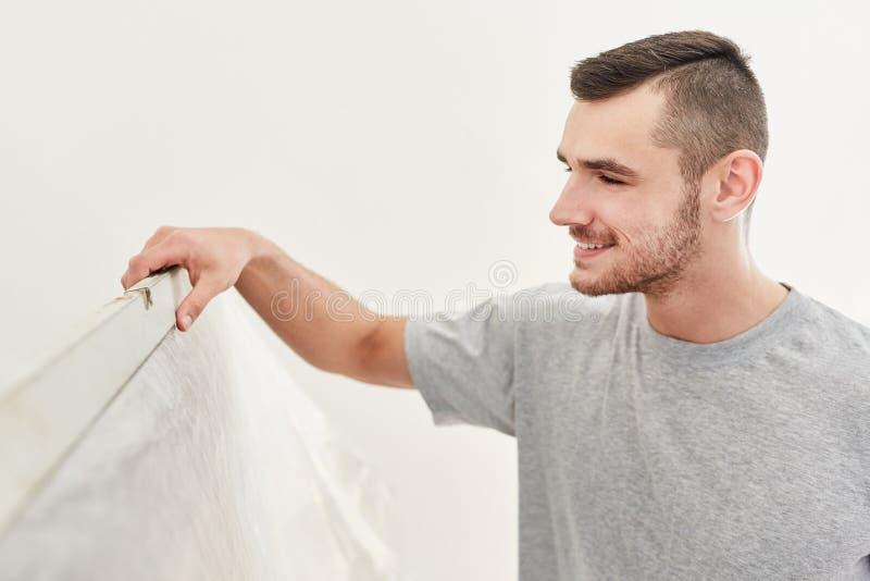Młody handyman z poziomem ducha na ścianie fotografia royalty free