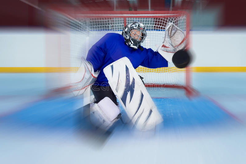 Młody hokejowy bramkarz łapie latającego krążek hokojowego obrazy royalty free