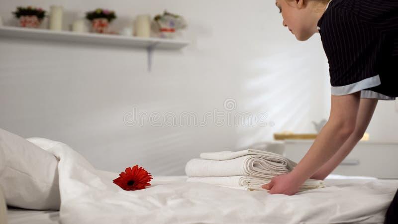 Młody housemaid bierze ręczniki daleko od dla pralni, czyści pokój hotelowy dla gości fotografia royalty free