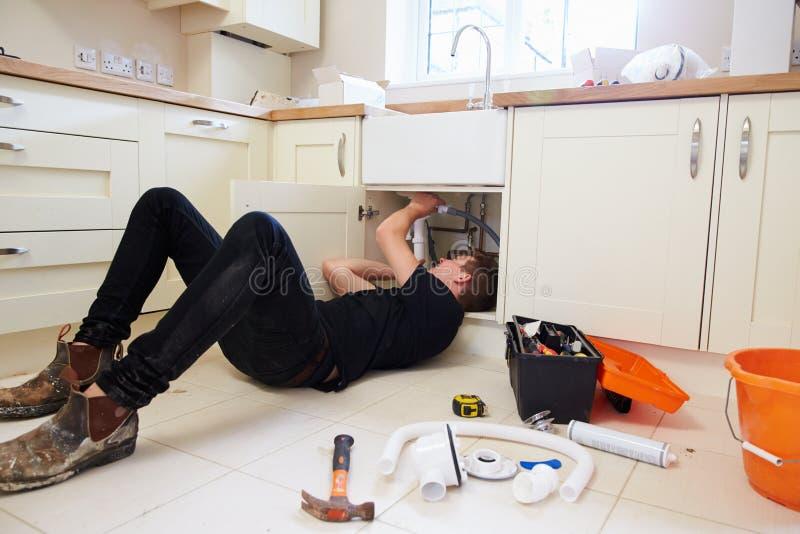 Młody hydraulik przy pracą pod kuchennym zlew, narzędzia w przedpolu zdjęcia stock