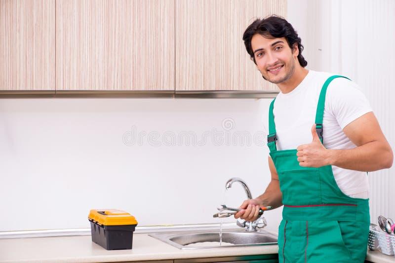 Młody hydraulika naprawiania klepnięcie przy kuchnią obraz stock