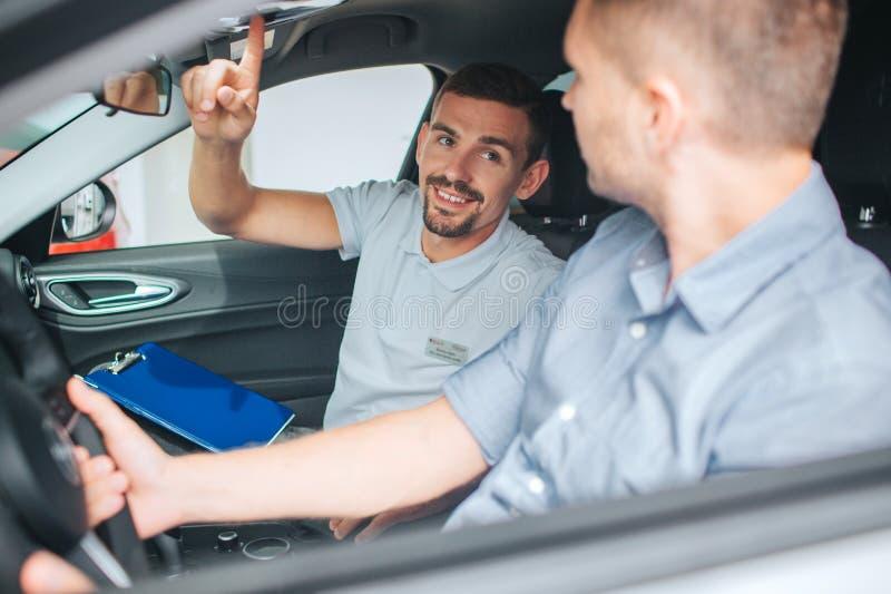 Młody i brodaty konsultant siedzi w samochodzie Patrzeje klienta i wskazuje up mężczyzna uśmiecha się potomstwa Kupujący siedzi n fotografia royalty free