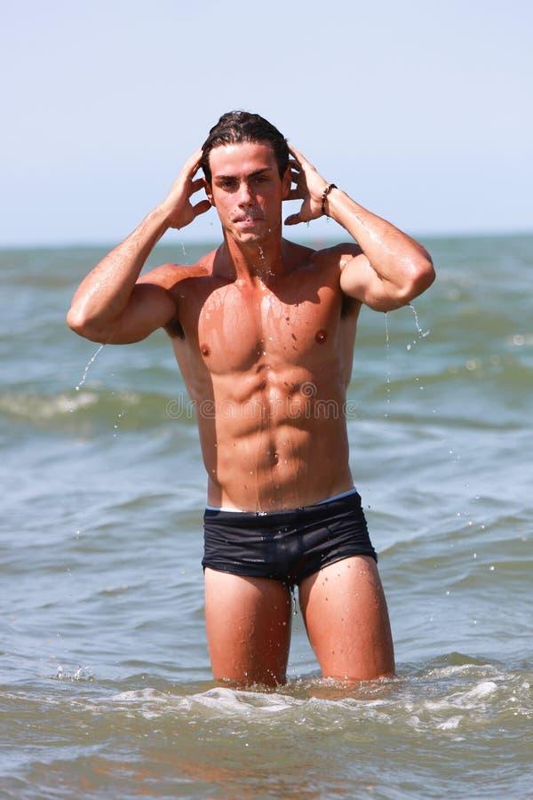Młody i mięśniowy mężczyzna w wody morskiej bawić się zdjęcie royalty free