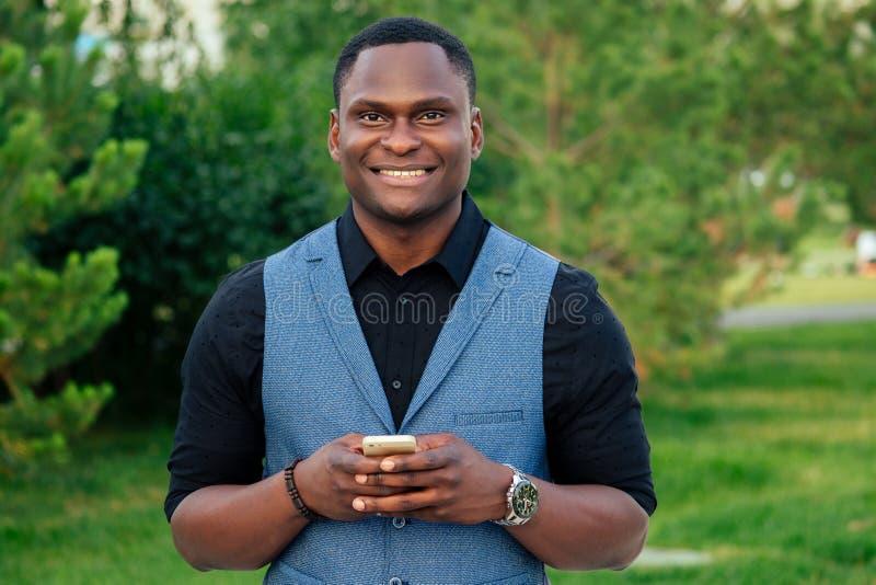 Młody i przystojny stylowy model afro- amerykański mężczyzna w stylowym garniturze w latynoskim parku latynoskim, latynoski bizne obrazy stock