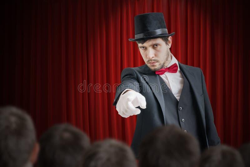 Młody iluzjonista lub magik wybieramy wolontariusza od widowni fotografia royalty free