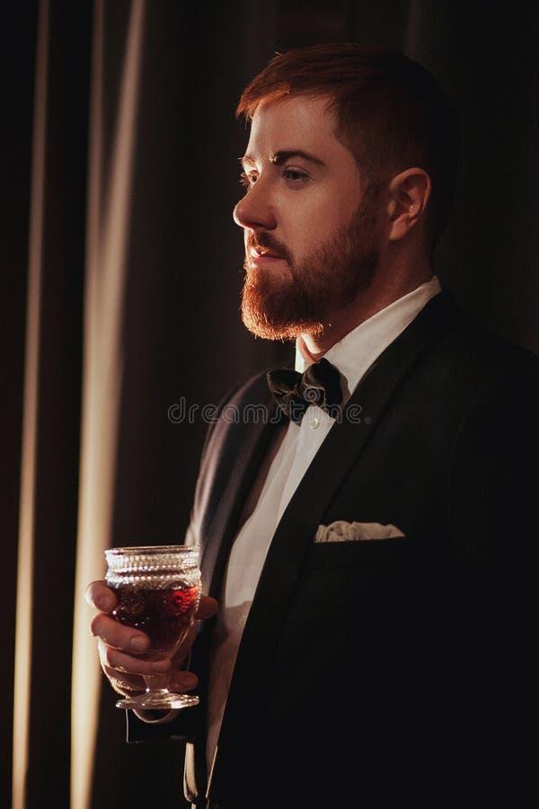 Młody imbirowy brodaty mężczyzna trzyma rocznika szklany z czerwonym winem przeciw światłu, czarnemu na tle Widoku profil zdjęcia royalty free