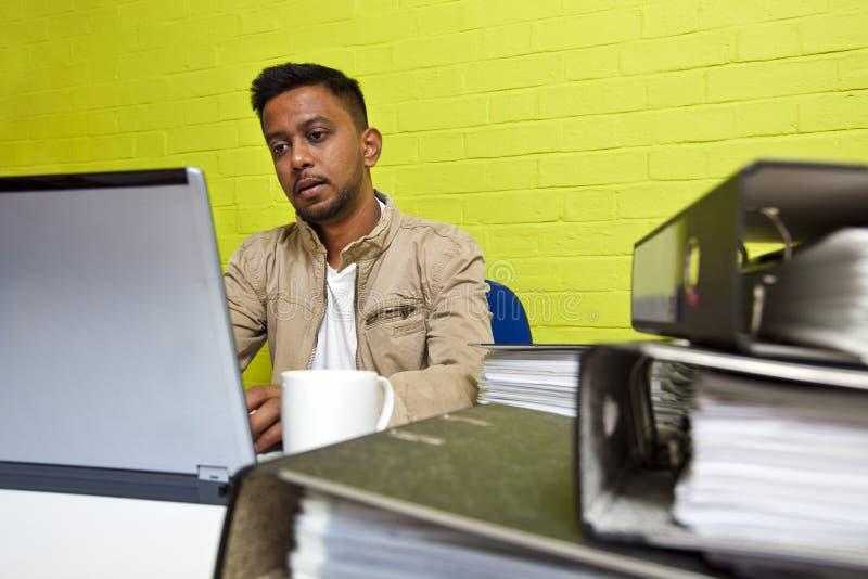 Młody Indiański mężczyzna pracuje przy jego komputerem otaczającym falcówkami zdjęcia stock