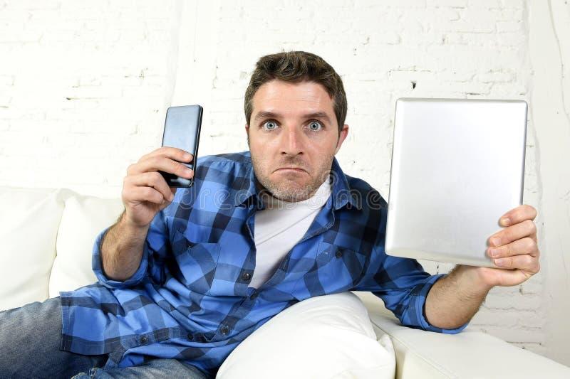 Młody interneta i technologii nałogowiec obsługuje networking z telefonem komórkowym i cyfrową pastylką zdjęcia stock