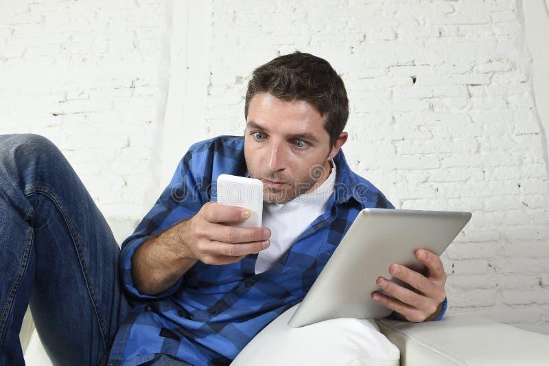 Młody interneta i technologii nałogowiec obsługuje networking z telefonem komórkowym i cyfrową pastylką obraz royalty free