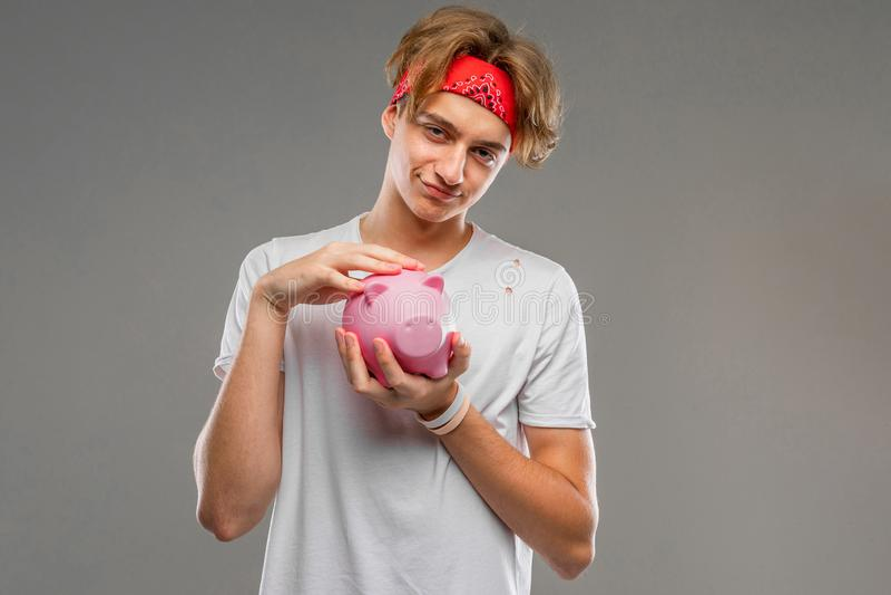 Młody kaukaski mężczyzna w czerwonych okularach słonecznych, biała koszulka z różowym pudełkiem na pieniądze świńskie, odizolowan obraz royalty free