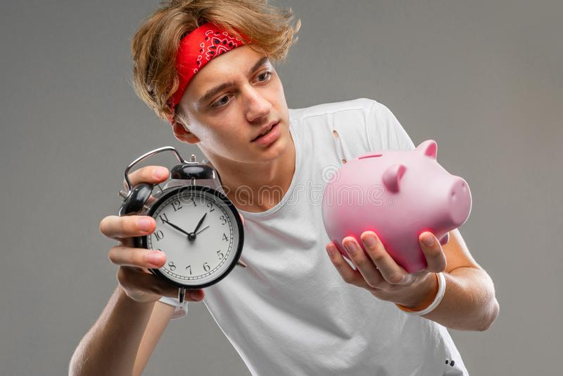 Młody kaukaski mężczyzna w czerwonych okularach słonecznych, biała koszulka z różowym pudełkiem na pieniądze świńskie, odizolowan fotografia royalty free