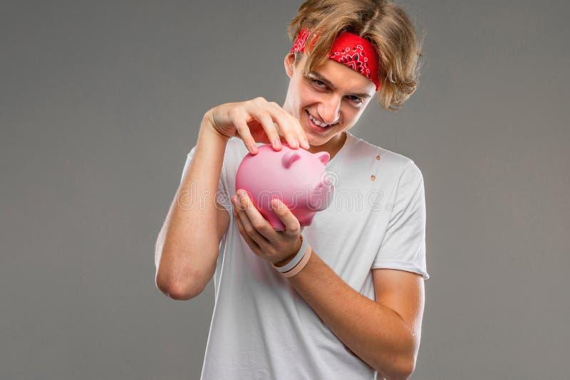 Młody kaukaski mężczyzna w czerwonych okularach słonecznych, biała koszulka z różowym pudełkiem na pieniądze świńskie, odizolowan zdjęcie stock