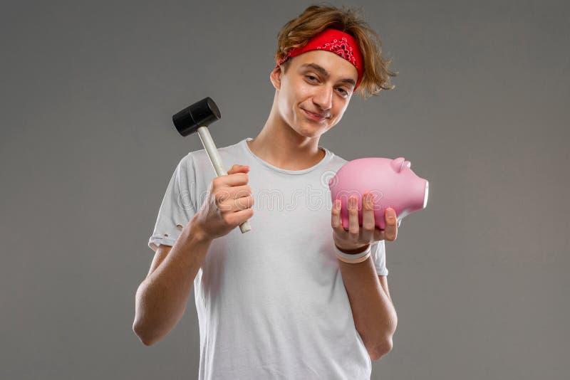 Młody kaukaski mężczyzna w czerwonych okularach słonecznych, biała koszulka z różowym pudełkiem na pieniądze świńskie, odizolowan fotografia stock