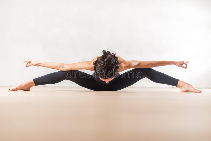 Młody Kaukaski tancerz robi posadzonemu szerokiemu noga chyłu ćwiczenia rozciągania kręgosłupowi i nogom naprzód obraz stock