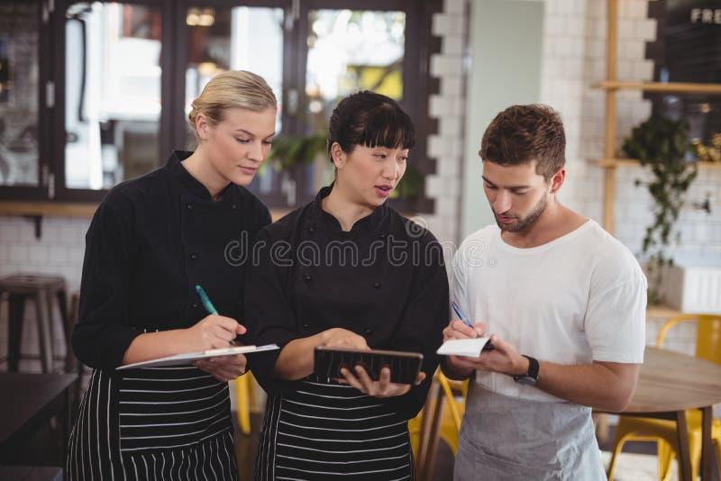 Młody kelner i kelnerka dyskutuje nad cyfrową pastylką zdjęcie stock