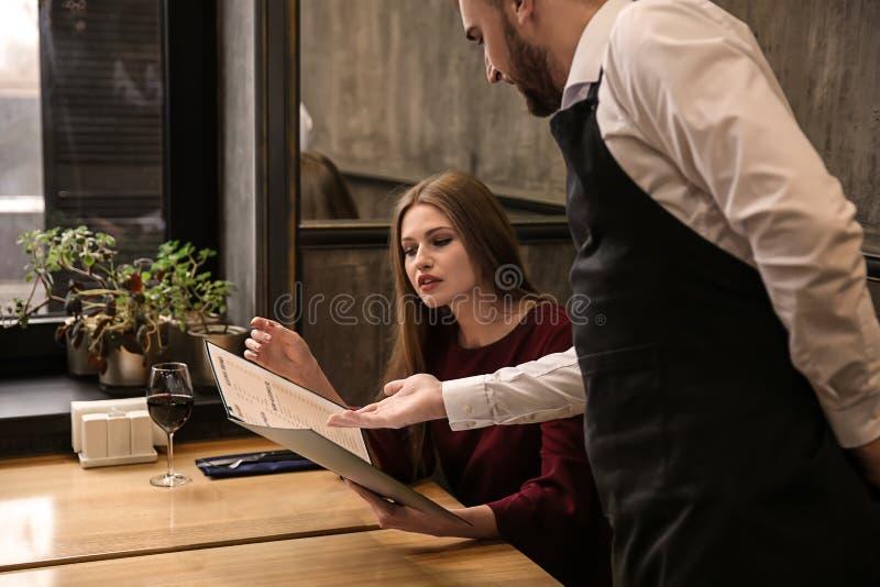 Młody kelner pokazuje kobiecie menu w restauracji fotografia stock