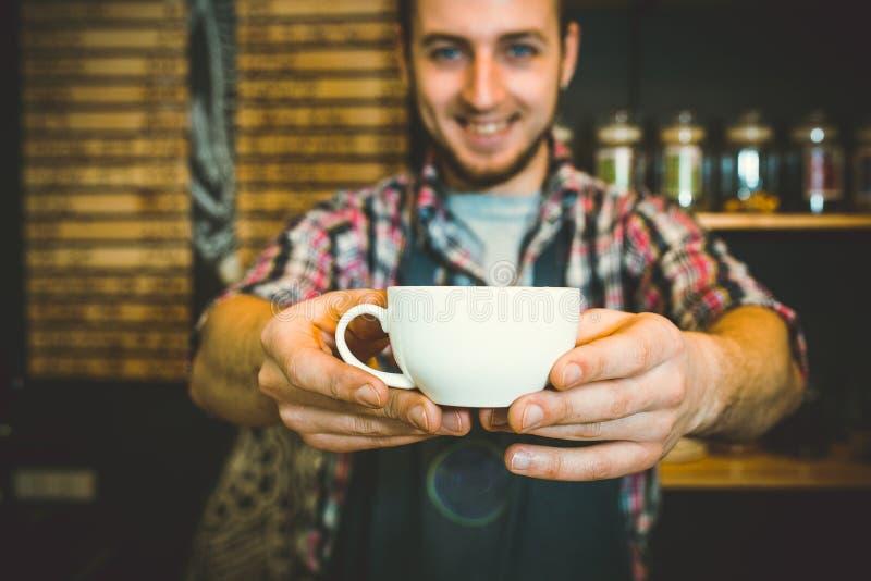Młody kelner uśmiecha się filiżankę kawy i trzyma obraz royalty free