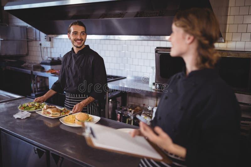 Młody kelnera narządzania jedzenie podczas gdy patrzejący kelnerki obrazy royalty free