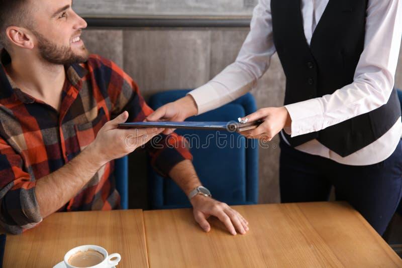 Młody kelnerka seansu mężczyzna menu w restauracji obrazy stock