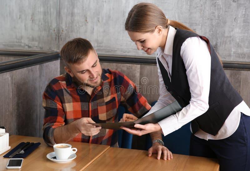 Młody kelnerka seansu mężczyzna menu w restauracji fotografia royalty free