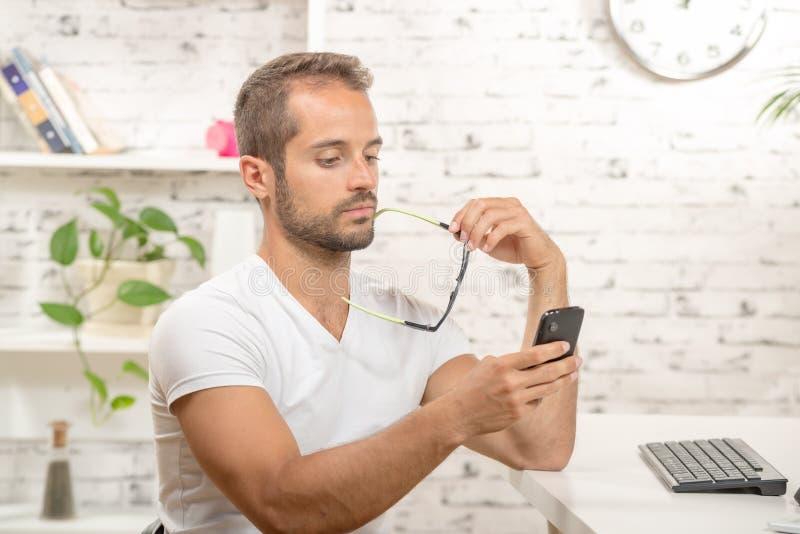 Młody kierownictwo patrzeje jego telefon komórkowego zdjęcia stock