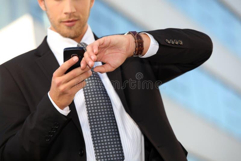 Młody kierownictwo sprawdza jego zegarek obrazy stock