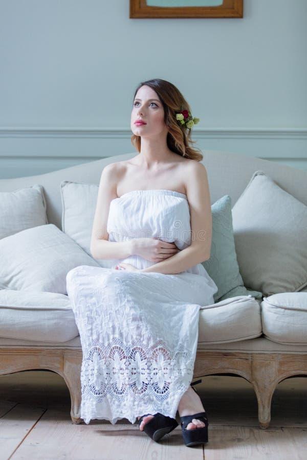 Młody kobieta w ciąży w biel sukni obsiadaniu obrazy stock