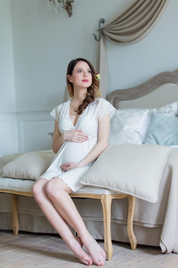 Młody kobieta w ciąży w biel sukni obsiadaniu zdjęcie royalty free