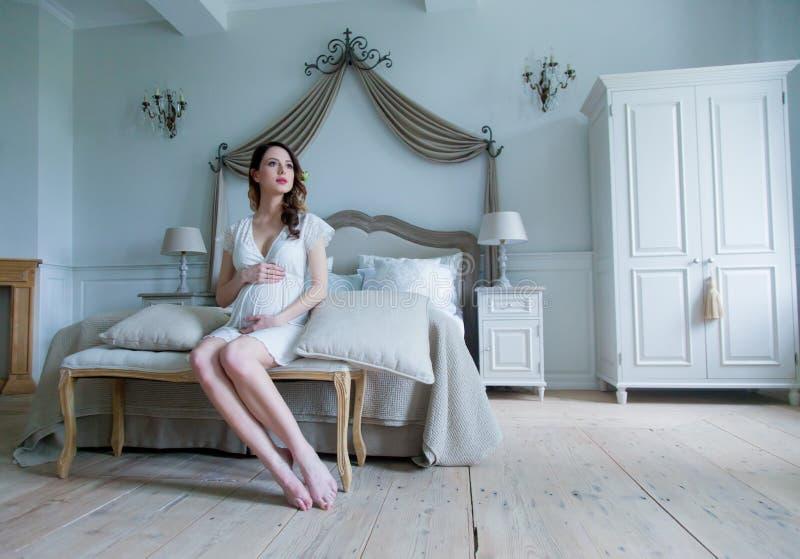 Młody kobieta w ciąży w biel sukni obsiadaniu obraz royalty free