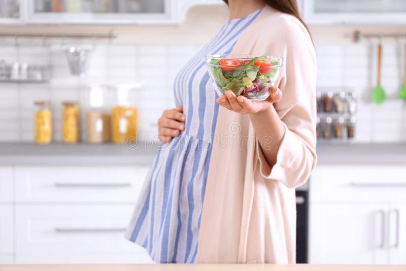 Młody kobieta w ciąży mienia puchar z sałatką obraz royalty free