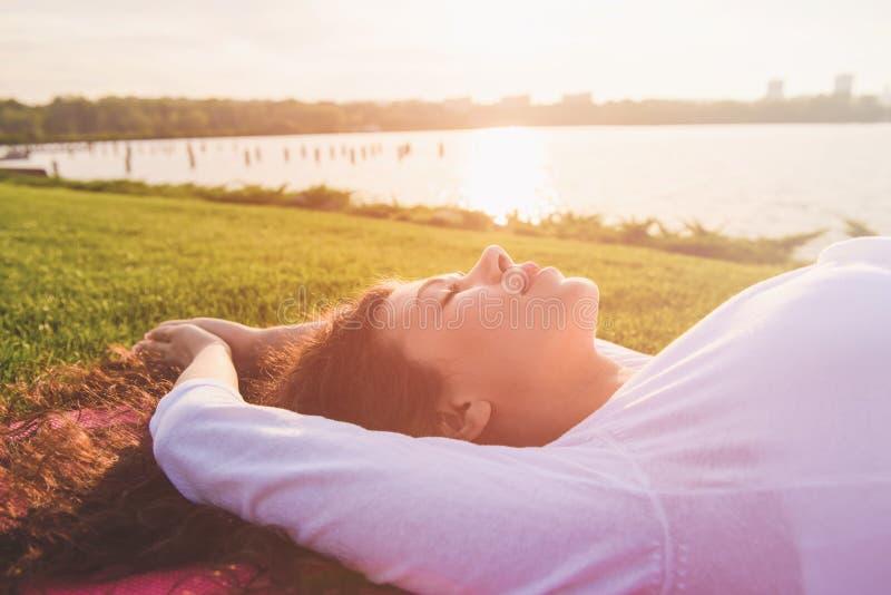 Młody kobieta w ciąży robi joga outdoors obraz stock