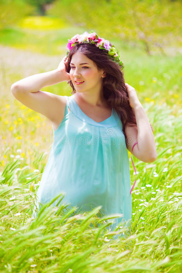 Młody kobieta w ciąży z długim kędzierzawym włosy w lecie obraz stock