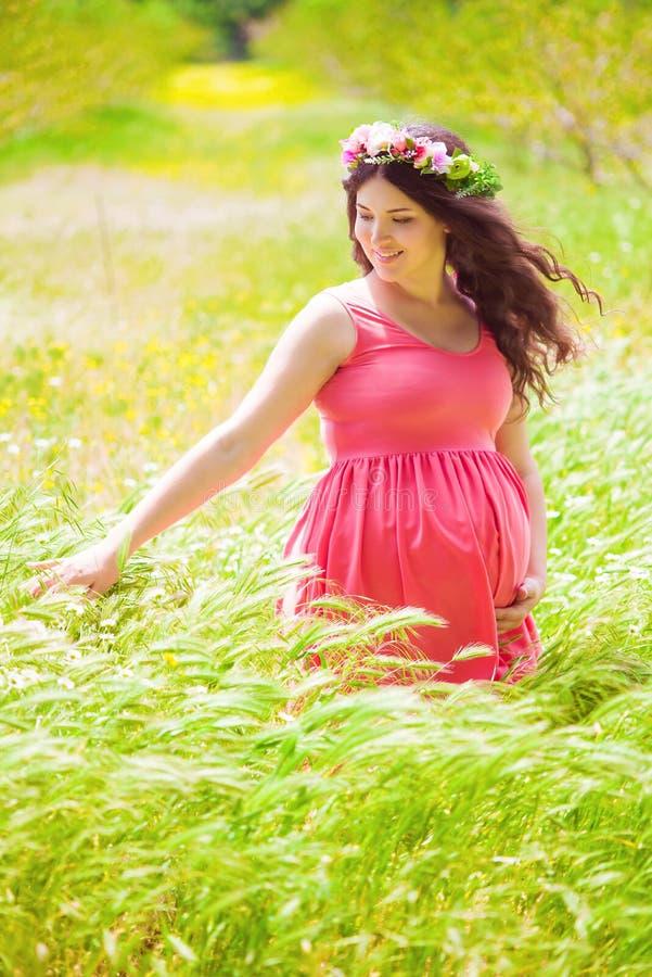 Młody kobieta w ciąży z długim kędzierzawym włosy w lecie fotografia stock