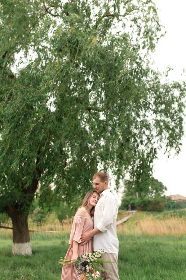 Młody kochający pary przytulenie, taniec na zielonej trawie na gazonie i Piękny i szczęśliwy dotyk kobiety i mężczyzny delikatnie obraz royalty free