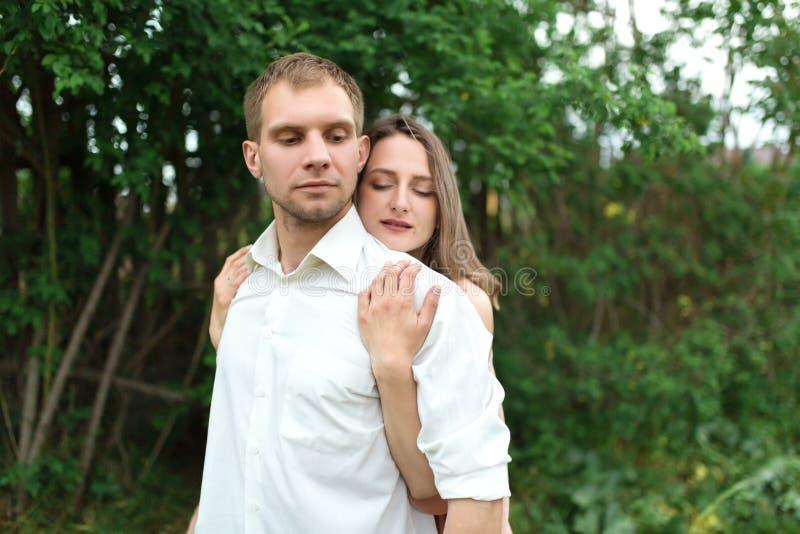 Młody kochający pary przytulenie, taniec na zielonej trawie na gazonie i Piękny i szczęśliwy dotyk kobiety i mężczyzny delikatnie obraz stock