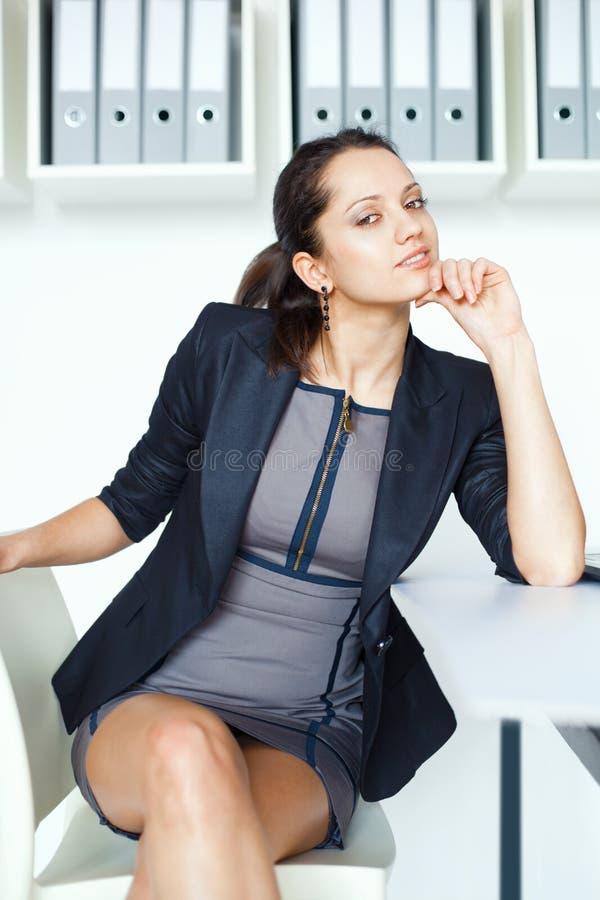 Młody kontemplacyjny biznesowej kobiety obsiadanie przy biurkiem fotografia stock