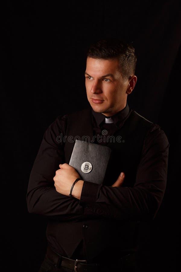 Młody księdza mienie i crypto biblia z bitcoin obraz stock
