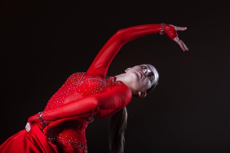 Młody latynoski flamenco tancerz w czerwieni sukni odizolowywającej na czarnym tle fotografia stock