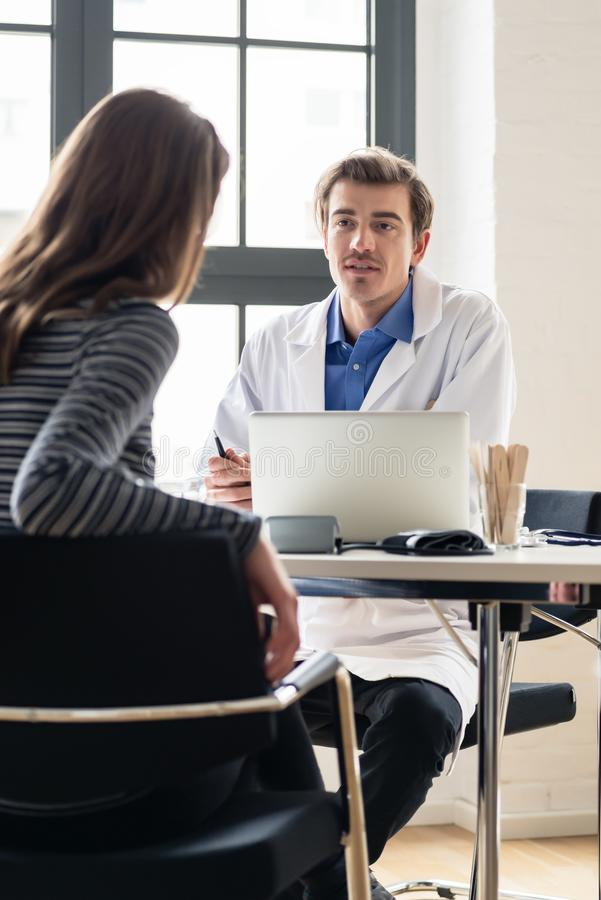 Młody lekarz słucha jego pacjent z szacunekiem i dedykacją zdjęcia royalty free