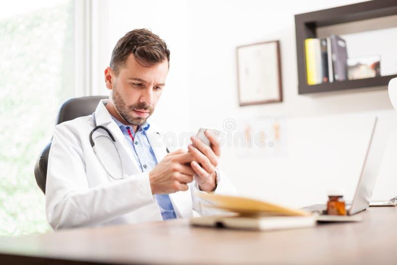 Młody lekarz używa smartphone zdjęcie stock