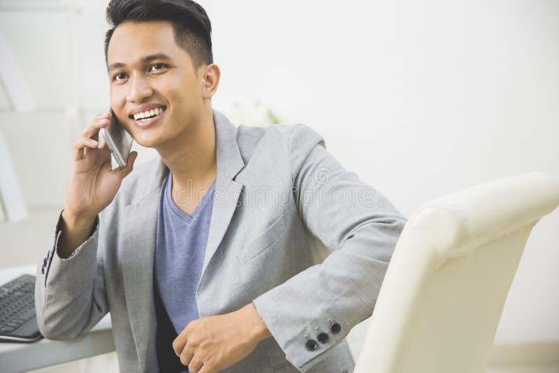 młody mądrze biznesowy mężczyzna opowiada na jego smartphone obraz royalty free