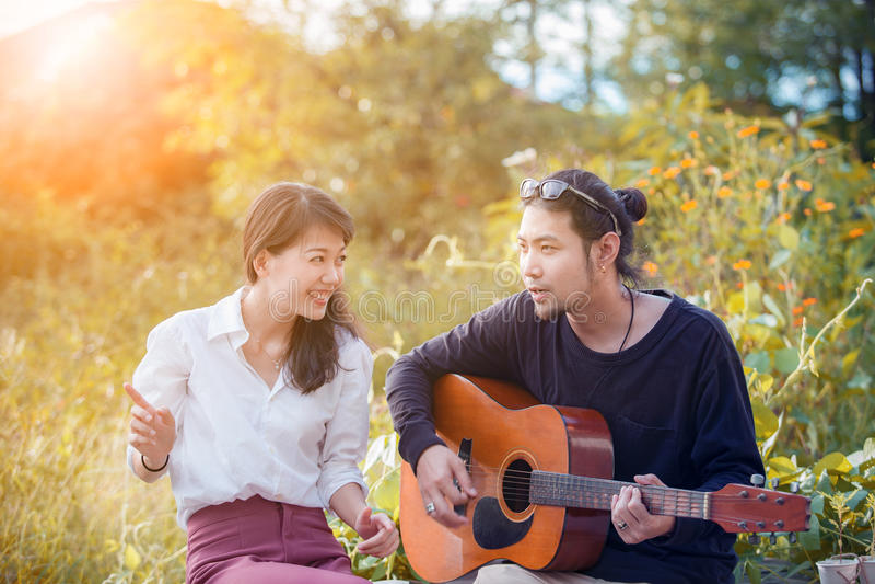 Młody mężczyzna, azjatykcia kobieta relaksuje i bawić się gitarę w parku zdjęcie royalty free