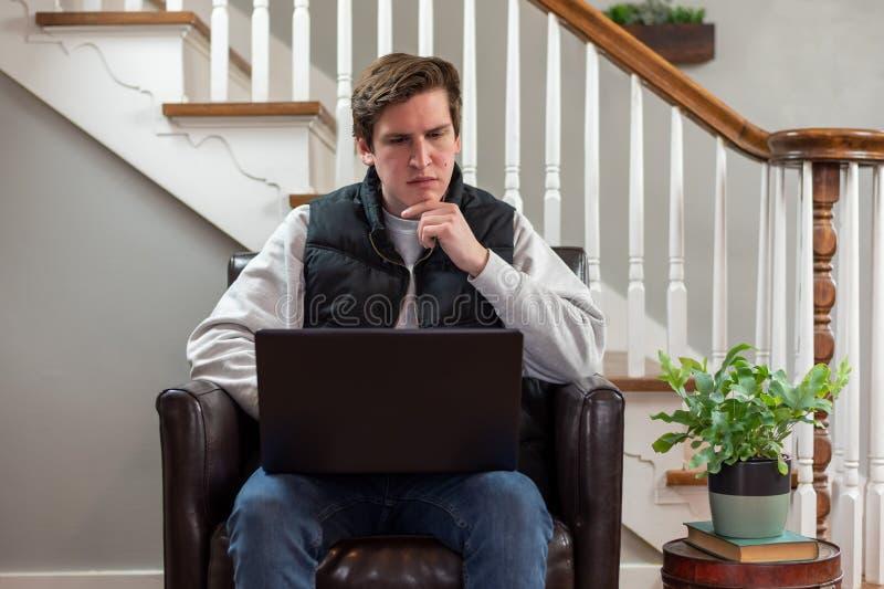 Młody mężczyzna korzystający z komputera przenośnego w domu obrazy stock