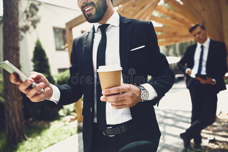 MÅ'ody mężczyzna trzymajÄ…cy filiżankÄ™ kawy, stojÄ…c ze smartfonem zdjęcia stock