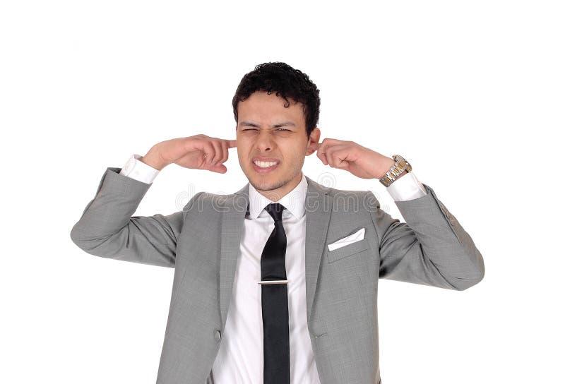 Młody mężczyzna trzymający palec w uchu zdjęcia royalty free