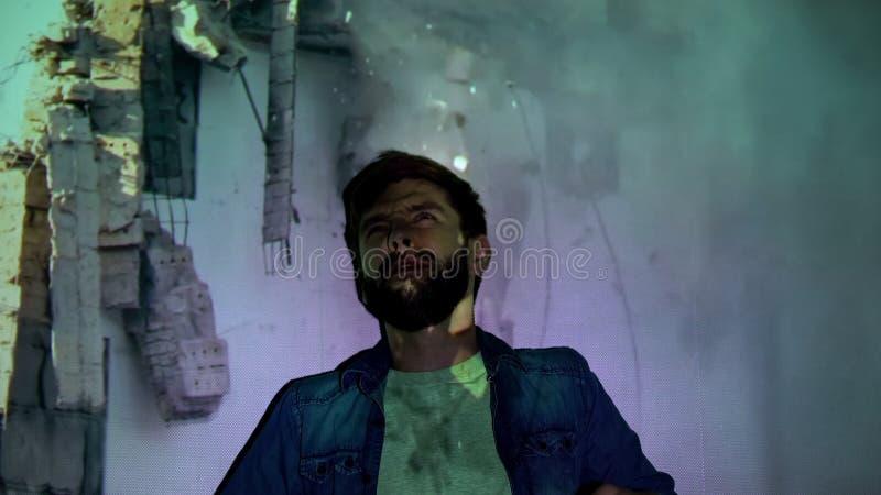 Młody mężczyzna umierający pod ruinami na tle, widząc halucynacje, trzęsienie ziemi fotografia stock
